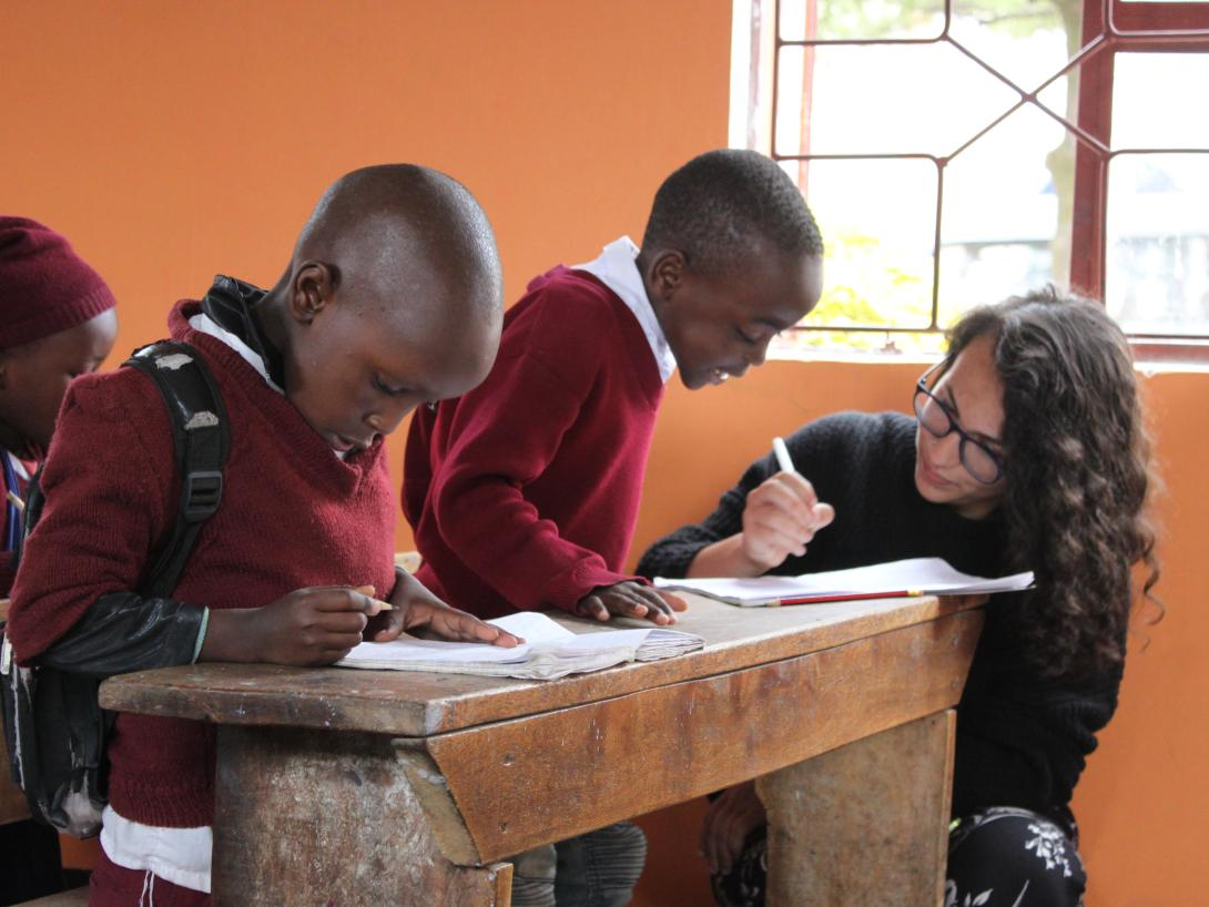 A volunteer teaching abroad, helps children with their classwork in Tanzania.